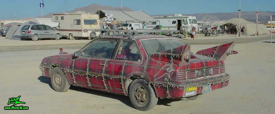 Photo of the Plaidmobile - Art Car / Mutant Vehicle, a 1985 Buick Skyhawk with a custom red plaid paint job, by Tim McNally in Black Rock City, Nevada, 2002. Tim McNally's Plaidmobile - Rear View