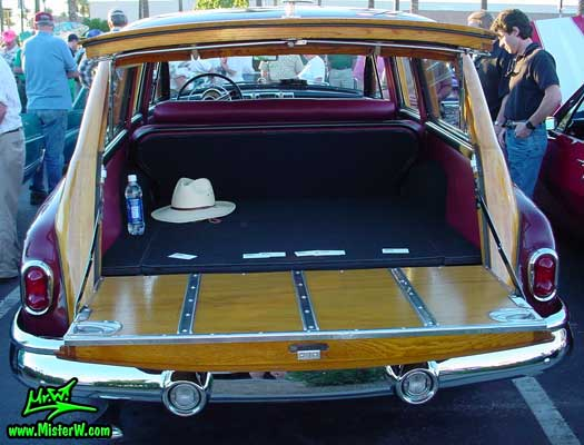 Photo of a maroon Buick Roadmaster Estate wagon, a Woodie station wagon with wood panels at the Scottsdale Pavilions Classic Car Show in Arizona. Rear view of a 1950 Buick Roadmaster Estate wagon