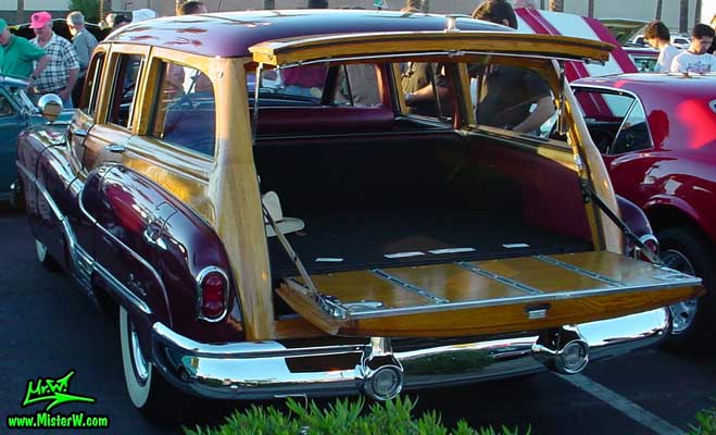 Photo of a maroon Buick Roadmaster Estate wagon, a Woodie station wagon with wood panels at the Scottsdale Pavilions Classic Car Show in Arizona. Back of a 1950 Buick Roadmaster woodie station wagon