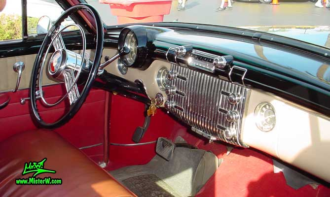 Photo of a forest green 1953 Buick Super Estate wagon, a Woodie station wagon with wood panels at the Scottsdale Pavilions Classic Car Show in Arizona. Interior & dashboard of a 1953 Buick Super station wagon