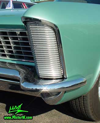 Photo of a mint green 1965 Buick Riviera 2 door hardtop coupe at the Scottsdale Pavilions Classic Car Show in Arizona. Front chrome trim & blinker of a 1965 Buick Riviera hardtop coupe
