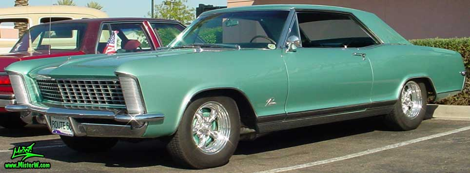 Photo of a mint green 1965 Buick Riviera 2 door hardtop coupe at the Scottsdale Pavilions Classic Car Show in Arizona. Side view of a 1965 Buick Riviera hardtop coupe