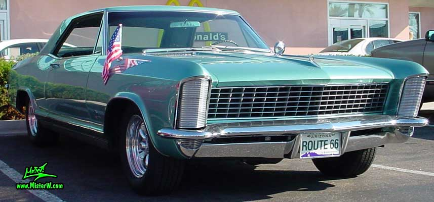 Photo of a mint green 1965 Buick Riviera 2 door hardtop coupe at the Scottsdale Pavilions Classic Car Show in Arizona. Front chrome grill & hidden headlights of a 1965 Buick Riviera hardtop coupe