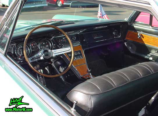 Photo of a mint green 1965 Buick Riviera 2 door hardtop coupe at the Scottsdale Pavilions Classic Car Show in Arizona. Dash board, seats & interior of a 1965 Buick Riviera hardtop coupe