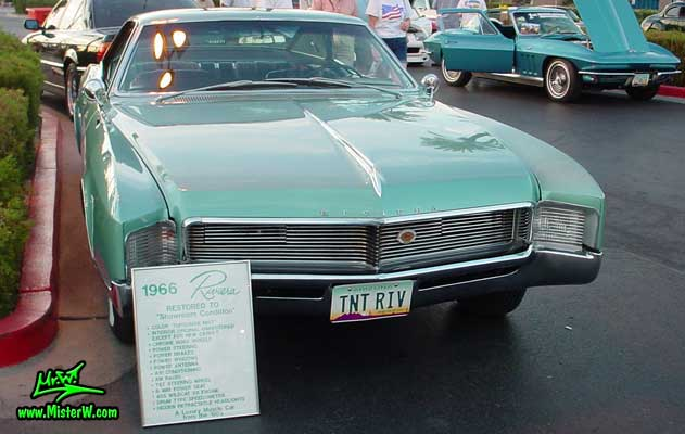 Photo of a mint green 1966 Buick Riviera 2 door hardtop coupe at the Scottsdale Pavilions Classic Car Show in Arizona. Front view of a 1966 Buick Riviera hardtop coupe