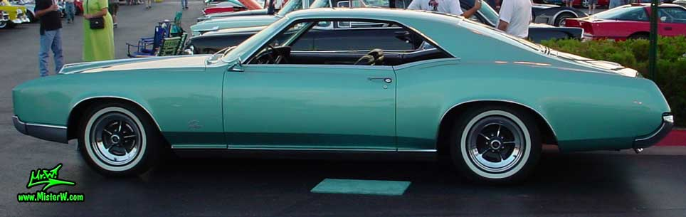 Photo of a mint green 1966 Buick Riviera 2 door hardtop coupe at the Scottsdale Pavilions Classic Car Show in Arizona. Side view of a 1966 Buick Riviera hardtop coupe