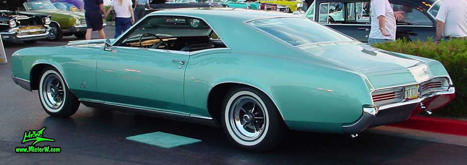 Photo of a mint green 1966 Buick Riviera 2 door hardtop coupe at the Scottsdale Pavilions Classic Car Show in Arizona. Tail of a 1966 Buick Riviera hardtop coupe