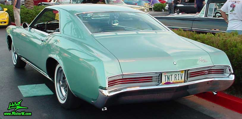 Photo of a mint green 1966 Buick Riviera 2 door hardtop coupe at the Scottsdale Pavilions Classic Car Show in Arizona. Back of a 1966 Buick Riviera hardtop coupe