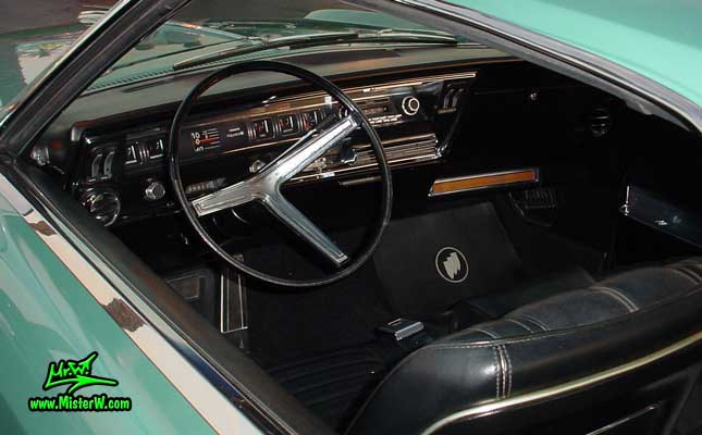Photo of a mint green 1966 Buick Riviera 2 door hardtop coupe at the Scottsdale Pavilions Classic Car Show in Arizona. Interior, dashboard & speedometer of a 1966 Buick Riviera