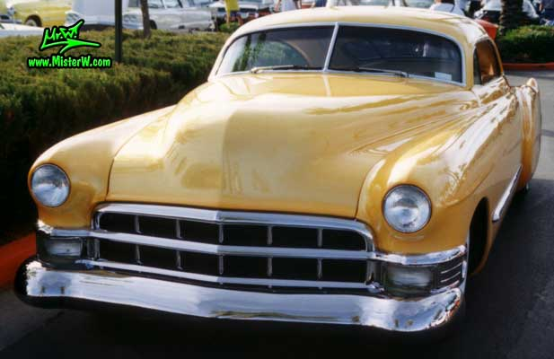 Photo of a yellow orange 1949 Custom Cadillac Sedanet Coupe 2 Door Fastback at the Scottsdale Pavilions Classic Car Show in Arizona. 1949 Custom Cadillac Sedanet Coupe 2 Door Fastback
