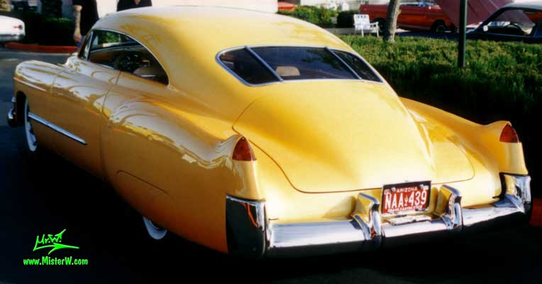 Photo of a powder yellow 1949 Custom Cadillac Sedanet 2 door fastback coupe at the Scottsdale Pavilions Classic Car Show in Arizona. Powder yellow top chopped 1949 Cadillac Low Rider