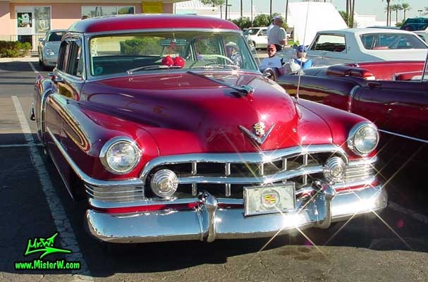 Photo of a cherry red 1950 Cadillac Series 62 4 door sedan at the Scottsdale Pavilions classic car show in Arizona. Red 1950 Cadillac sedan