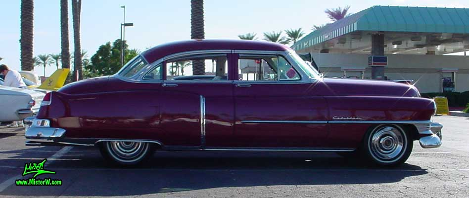 Photo of a cherry red 1950 Cadillac Series 62 4 door sedan at the Scottsdale Pavilions classic car show in Arizona. 1950 Cadillac sedan sideview