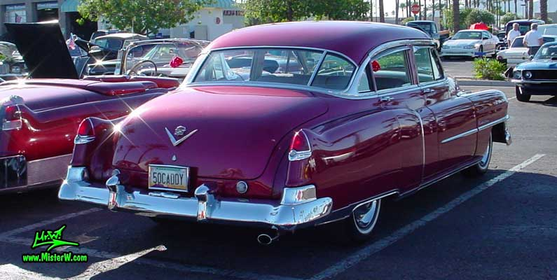 Photo of a cherry red 1950 Cadillac Series 62 4 door sedan at the Scottsdale Pavilions classic car show in Arizona. Red 1950 Cadillac sedan fins