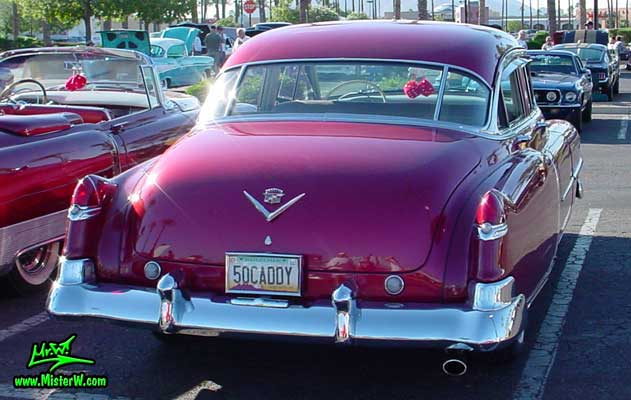 Photo of a cherry red 1950 Cadillac Series 62 4 door sedan at the Scottsdale Pavilions classic car show in Arizona. 1950 Cadillac tail fins