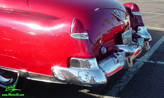 Photo of a cherry red 1950 Cadillac Series 62 4 door sedan at the Scottsdale Pavilions classic car show in Arizona. Tail fins of a 1950 Cadillac