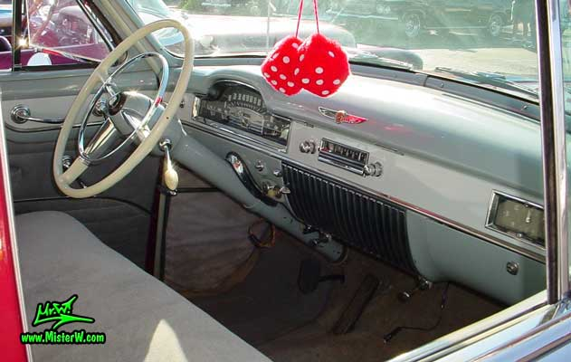 Photo of a cherry red 1950 Cadillac Series 62 4 door sedan at the Scottsdale Pavilions classic car show in Arizona. Dashboard of a 1950 Cadillac