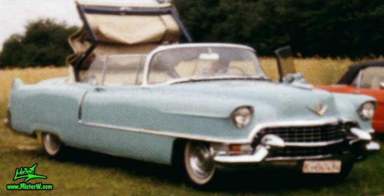 Photo of a turquoise 1955 Cadillac Series 62 Convertible at a classic car meeting in Köln Chorweiler (Cologne), Germany. 1955 Cadillac Convertible with the top closing