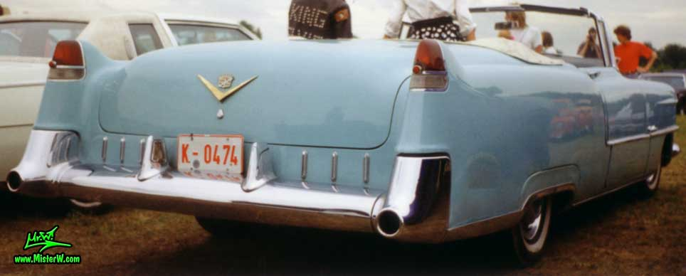 Photo of a turquoise 1955 Cadillac Series 62 Convertible at a classic car meeting in Köln Chorweiler (Cologne), Germany. Tail Fins & Rear Lights of a turquoise 1955 Cadillac Convertible in Germany