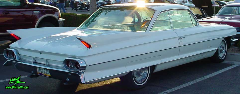 Photo of a white 1961 Cadillac 2 Door Hardtop Coupe at the Scottsdale Pavilions Classic Car Show in Arizona. 1961 Cadillac Fins