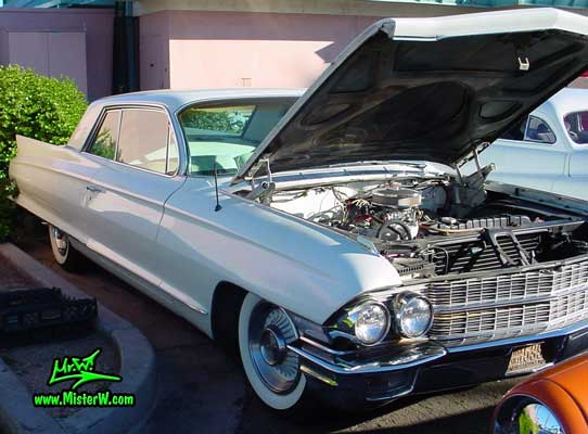 Photo of a white 1962 Cadillac 2 Door Hardtop Coupe at the Scottsdale Pavilions Classic Car Show in Arizona. 1962 Cadillac engine under hood photo