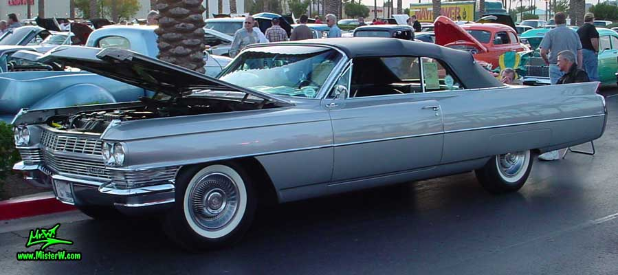 Photo of a silver grey 1964 Cadillac Convertible at the Scottsdale Pavilions Classic Car Show in Arizona. 1964 Cadillac Convertible with open hood