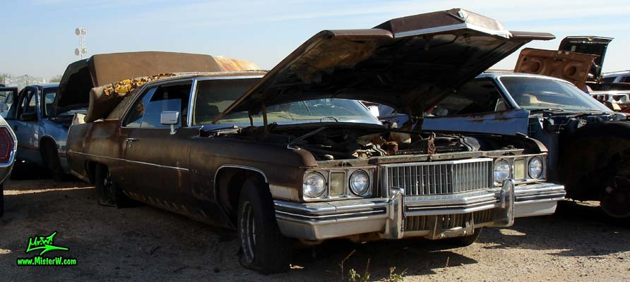 Photo of a brown 1973 Cadillac 2 door hardtop Coupe DeVille at a junk yard in Phoenix, Arizona. Front of a 1973 Cadillac Coupe DeVille