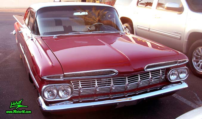 Photo of a red 1959 Chevrolet 2 Door Hardtop Coupe at the Scottsdale Pavilions Classic Car Show in Arizona. Front view of a 59 Chevrolet 2 Door Hardtop Coupe
