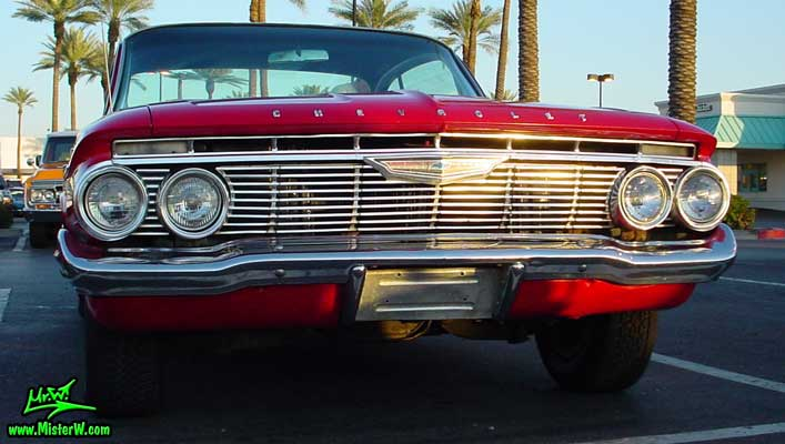 Photo of a red 1961 Chevrolet Impala 2 Door Hardtop Coupe at the Scottsdale Pavilions Classic Car Show in Arizona. Chrome Grill of a 1961 Chevrolet Impala