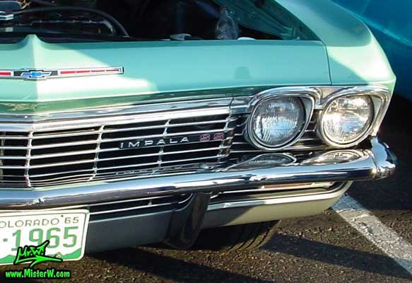 Photo of a turquoise 1965 Chevrolet Impala 2 Door Hardtop Coupe at the Scottsdale Pavilions Classic Car Show in Arizona. Head Lights of a 1965 Chevrolet Impala Coupe