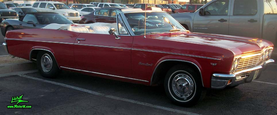 Photo of a red 1966 Chevrolet Impala Super Sport convertible at the Scottsdale Pavilions Classic Car Show in Arizona. Side view of a 1966 Chevrolet Impala Super Sport convertible