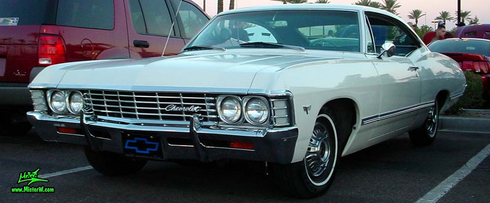 Photo of a white 1967 Chevrolet Impala 2 Door Hardtop Coupe at the Scottsdale Pavilions Classic Car Show in Arizona. 1967 Chevy Impala Coupe