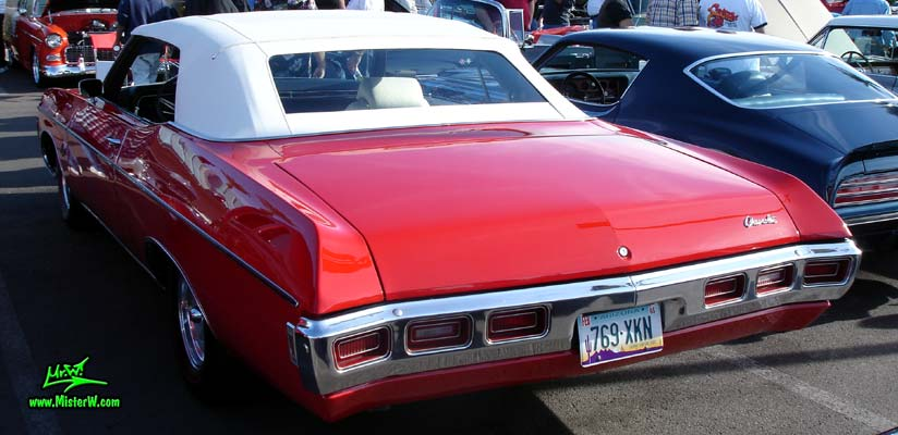 Photo of a red 1969 Chevrolet Impala convertible at the Scottsdale Pavilions Classic Car Show in Arizona. Rear view of a 1969 Chevrolet Impala convertible