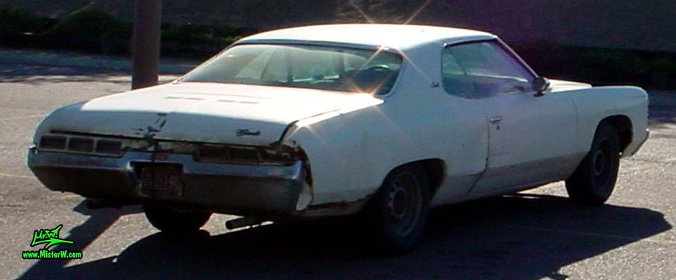 Photo of a beat up white & rusty 1971 Chevrolet 2 door hardtop coupe in Phoenix, Arizona. Rearview of a 1971 Chevrolet Coupe
