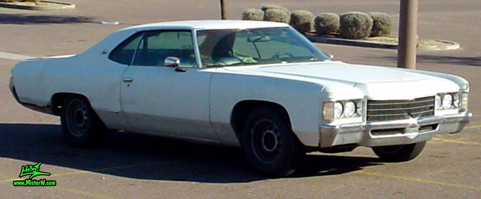 Photo of a beat up white & rusty 1971 Chevrolet 2 door hardtop coupe in Phoenix, Arizona. Sideview of a 1971 Chevrolet Coupe
