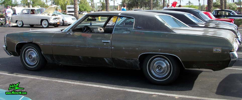 Photo of a beat up brown & rusty 1972 Chevrolet 2 door hardtop coupe at the Scottsdale Pavilions Classic Car Show in Arizona. Side view of a 1972 Chevrolet Coupe