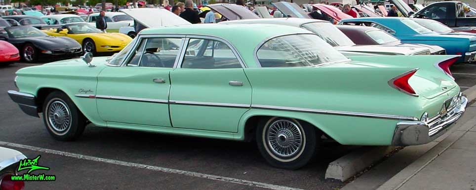 Photo of a turquoise 1960 Chrysler 4 door sedan at the Scottsdale Pavilions Classic Car Show in Arizona. Side view of a 1960 Chrysler
