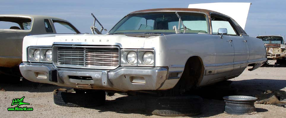 Photo of a white 1973 Chrysler New Yorker 4 door hardtop sedan at a junk yard in Phoenix, Arizona. Front view of a 1973 Chrysler New Yorker hardtop sedan