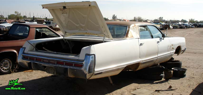 Photo of a white 1973 Chrysler New Yorker 4 door hardtop sedan at a junk yard in Phoenix, Arizona. Rear view of a 1973 Chrysler New Yorker hardtop sedan