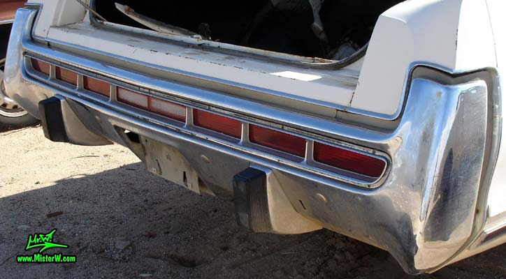 Photo of a white 1973 Chrysler New Yorker 4 door hardtop sedan at a junk yard in Phoenix, Arizona. Rear bumper & tail lights of a 1973 Chrysler New Yorker hardtop sedan