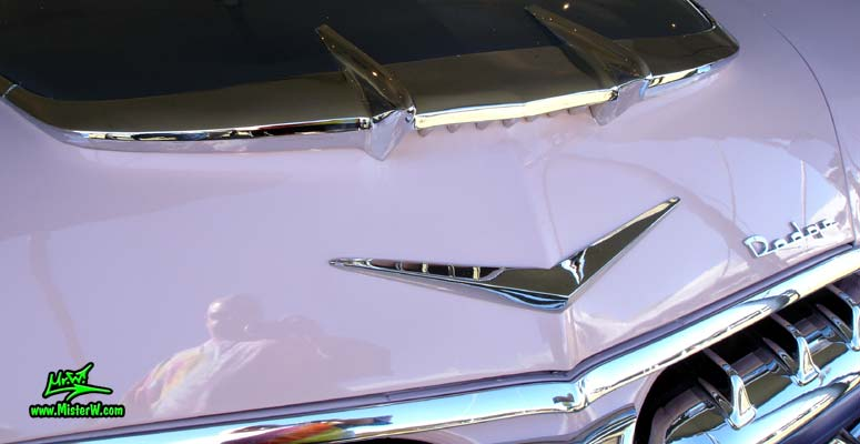 Photo of a white, pink & charcoal grey 1956 Chrysler Dodge Royal 4 Door Sedan at a Classic Car Auction in Scottsdale, Arizona. Chrome Hood Ornament of a 1956 Dodge Royal