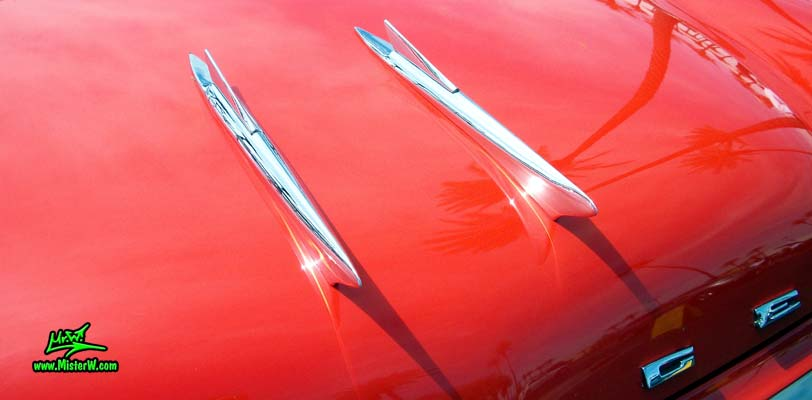 Photo of a red & white 1958 Chrysler Dodge Coronet 2 Door Hardtop Coupe at the Scottsdale Pavilions Classic Car Show in Arizona. Hood Ornaments of a 1958 Dodge Coronet Coupe