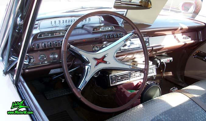 Photo of a pink 1960 Dodge Pioneer 4 door sedan at the Scottsdale Pavilions Classic Car Show in Arizona. Steering wheel & dash of a 1960 Dodge Pioneer sedan