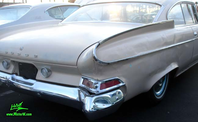 Photo of a tan 1961 Dodge 2 door hardtop coupe at the Scottsdale Pavilions Classic Car Show in Arizona. Tailfin of a 1961 Dodge coupe
