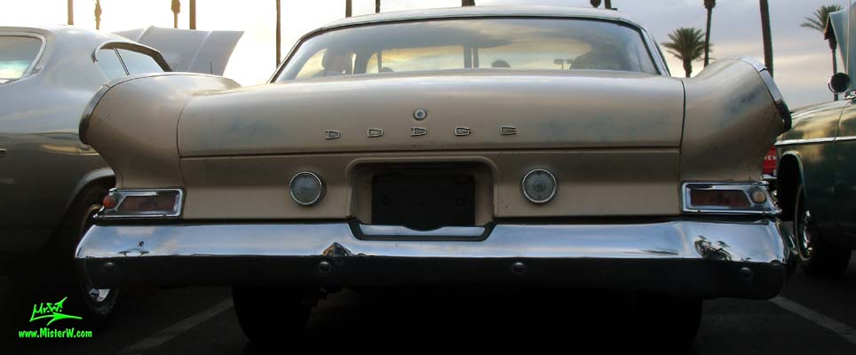 Photo of a tan 1961 Dodge 2 door hardtop coupe at the Scottsdale Pavilions Classic Car Show in Arizona. Rearview of a 1961 Dodge coupe