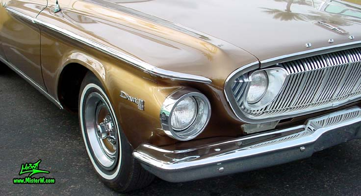 Photo of a brown 1962 Dodge Dart 4 door station wagen at the Scottsdale Pavilions Classic Car Show in Arizona. Head light & blinker of a 1962 Dodge Dart