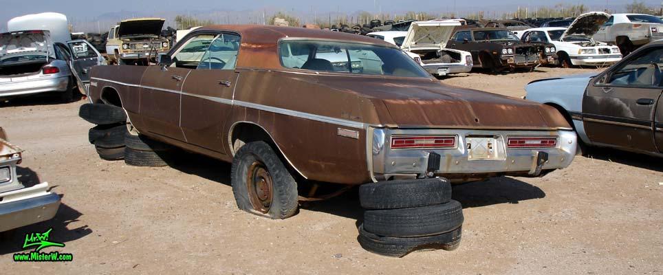 Photo of a brown 1973 Dodge Monaco 4 door hardtop sedan at a junk yard in Phoenix, Arizona. Rearview of a 1973 Dodge Monaco Hardtop Sedan