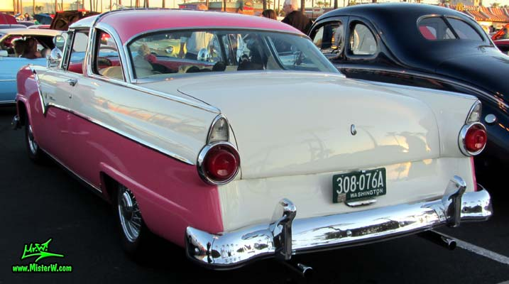 Photo of a pink & white 1955 Ford Crown Victoria 2 Door Hardtop Coupe at the Scottsdale Pavilions Classic Car Show in Arizona. Rearview of a 1955 Ford Crown Victoria Hardtop Coupe