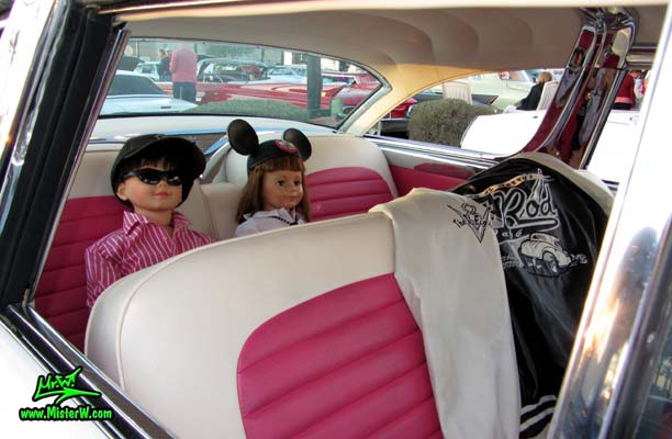 Photo of a pink & white 1955 Ford Crown Victoria 2 Door Hardtop Coupe at the Scottsdale Pavilions Classic Car Show in Arizona. 1955 Ford Coupe with Life Size Kids Dolls in the Back Seat