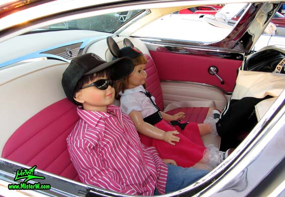 Photo of a pink & white 1955 Ford Crown Victoria 2 Door Hardtop Coupe at the Scottsdale Pavilions Classic Car Show in Arizona. Life Size Kids Dolls in a 55 Ford Coupe